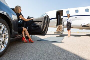 Wealthy Woman Stepping Out Of Car At Terminal